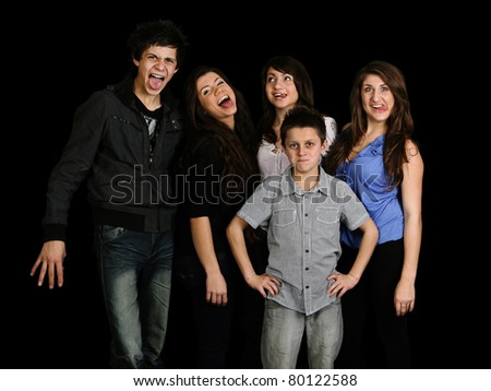 family of five siblings pulling funny faces - stock photo