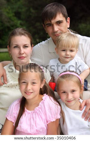 family of five with serious parents outdoor in summer - stock photo