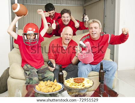 Family of football fans cheering for their favorite team. - stock photo