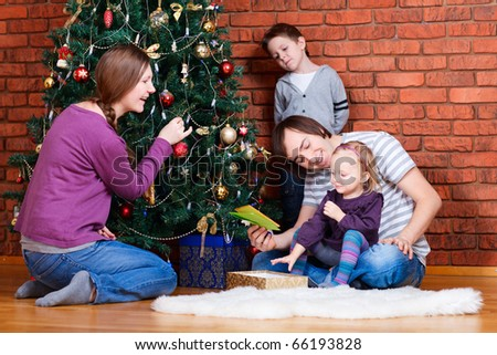 Family of four at home decorating Christmas tree - stock photo