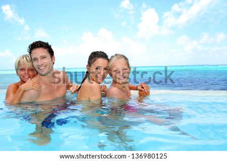Family of four bathing in swimming pool - stock photo