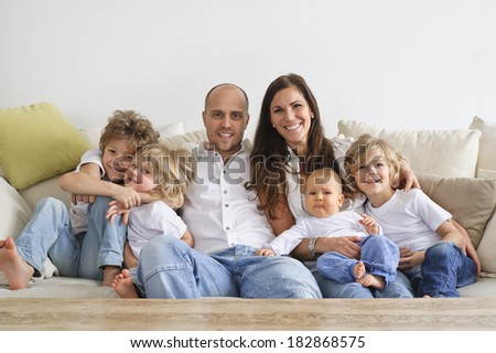 Family of four brothers and their parents sitting on a sofa