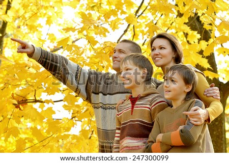 Family of four enjoying golden leaves in autumn park,man shows something - stock photo