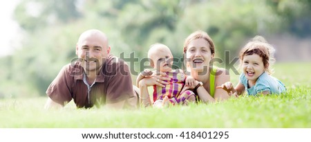 family of four enjoying time at green grass in summer park - stock photo