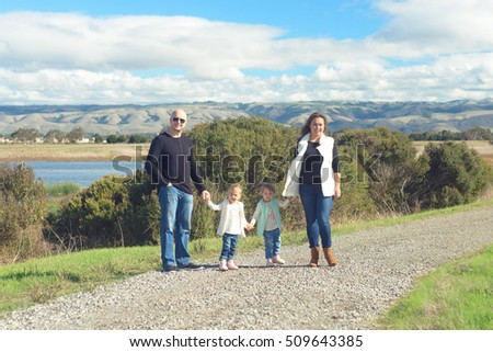 Family of four - father, mother and two toddler daughters - walking on beautiful trail in the hills enjoying sunny day.