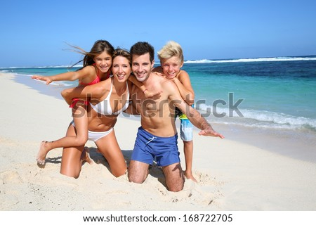 Family of four having fun at the beach - stock photo