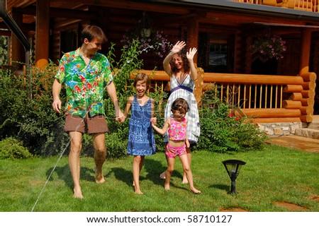 Family of four having fun in the garden - stock photo