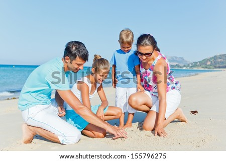 Family of four having fun on tropical beach