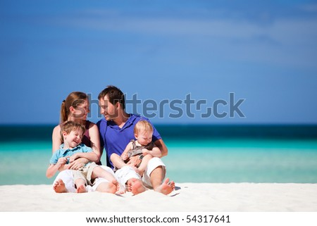 Family of four having fun on tropical beach - stock photo