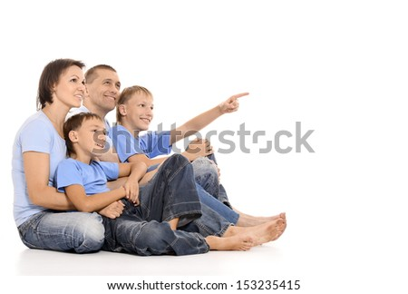 Family of four having fun sitting on a floor on white background - stock photo