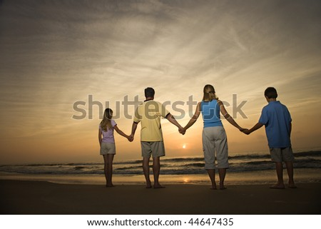 Family of four holding hands on beach watching the sunset. Horizontally framed shot. - stock photo