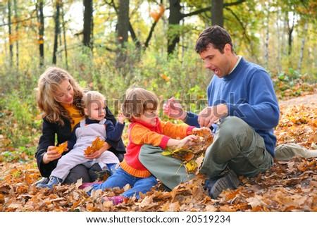 Family of four in forest in autumn - stock photo
