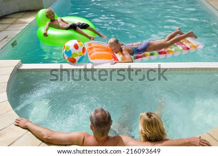 Family of four in swimming pool, boy and girl (7-11) on inflatable chair and bed - stock photo