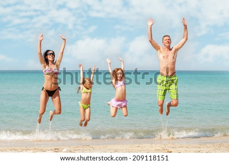 Family of four jumping at beach