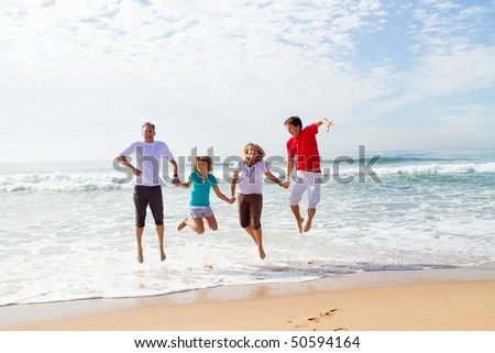 family of four jumping on beach