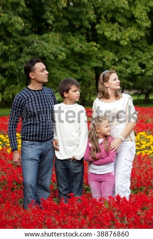 family of four looking aside in flowering park - stock photo