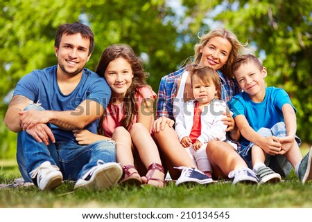 Family of four looking at camera outdoors - stock photo