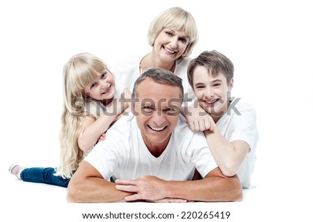 Family of four lying on top of each other  and posing to camera