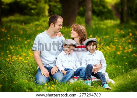 Family of four, mother, father and two boys, parent looking at each other, laughing, smiling, hugging, giving a kiss, holding flowers