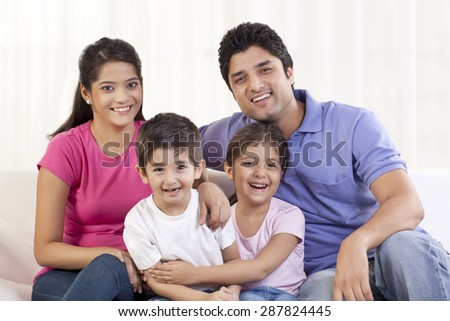 Family of four on sofa - stock photo