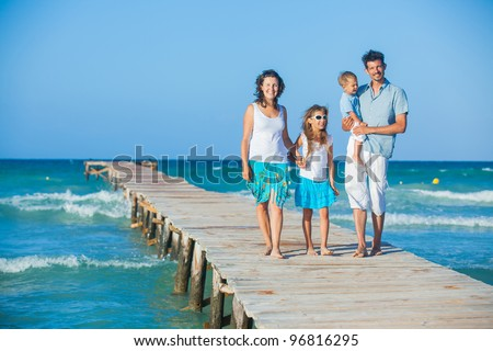 Family of four on wooden jetty by the ocean - stock photo