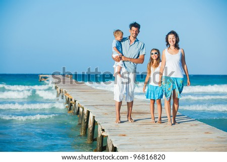 Family of four on wooden jetty by the ocean