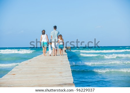 Family of four on wooden jetty by the ocean. Back view - stock photo