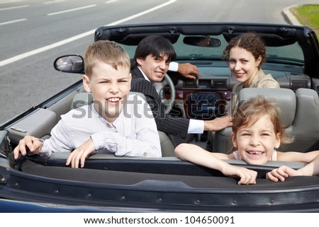 Family of four - parents and two children -  sits in a cabriolet, standing on the roadside, everybody look back, rear view, focus on children