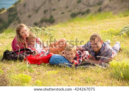 Family of four people looking to beautiful seascape in mountains