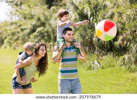 Family of four playing with ball in summer park - stock photo