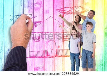 Family of four pointing at copy space against digitally generated grey wooden planks - stock photo