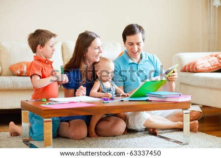 Family of four reading and drawing together at home