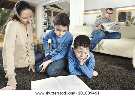 Family of four reading in their home's living room. - stock photo