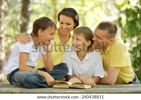 Family of four reading outdoors at table with book - stock photo