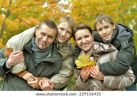 family of four relaxing in the park in autumn - stock photo