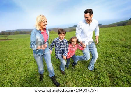 Family of four running together in natural landscape - stock photo