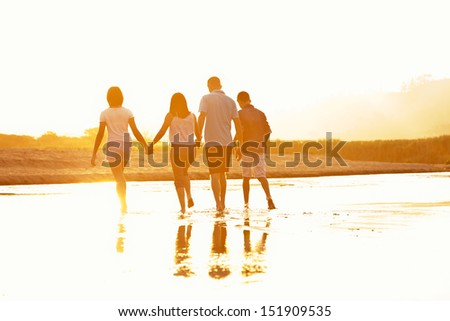 Family of four silhouette by a sunset walking at the beach - stock photo