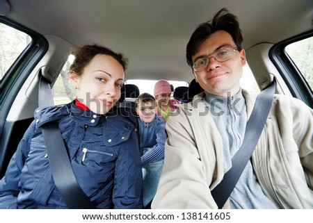 Family of four sits in car, children on backseat - stock photo