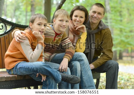 Family of four sitting on a bench in autumn park