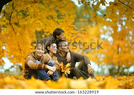 Family of four sitting on a bench in autumn park - stock photo