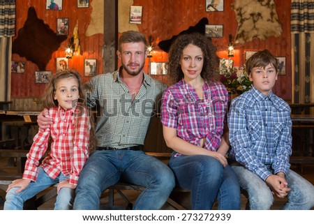 family of four sitting on a bench on background of wall with pelts - stock photo