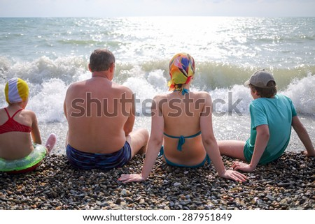 family of four sitting on a pebble beach - stock photo