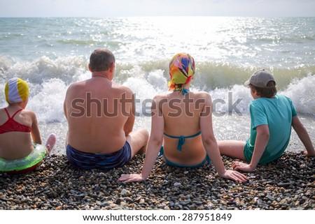 family of four sitting on a pebble beach - stock photo