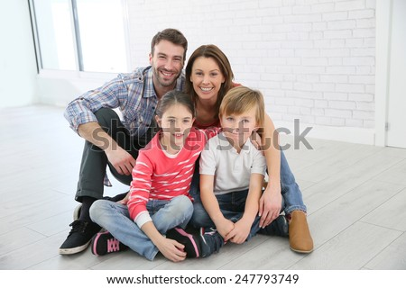 Family of four sitting on the floor - stock photo