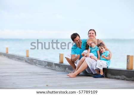 Family of four sitting on wooden jetty by the ocean - stock photo