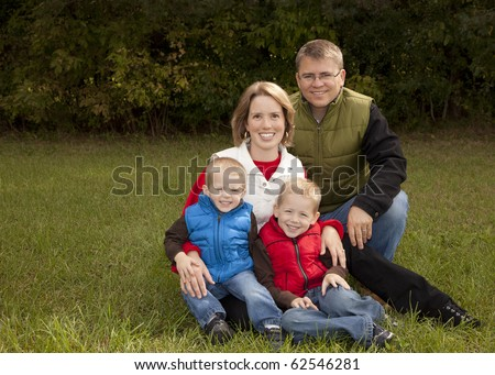 Family of Four Sitting Together Outside - stock photo