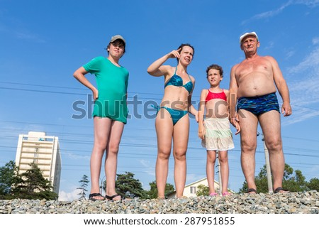 family of four standing on a railway embankment - stock photo