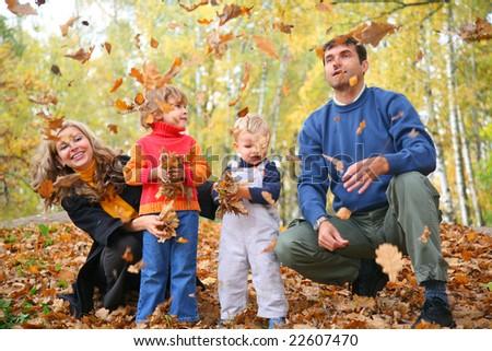 family of four throw autumnal leaves - stock photo