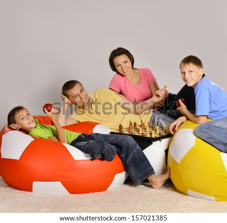 Family of four watching tv sitting on colored cushions - stock photo