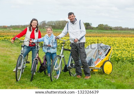Family of four with bicycle on a spring day in Holland - stock photo